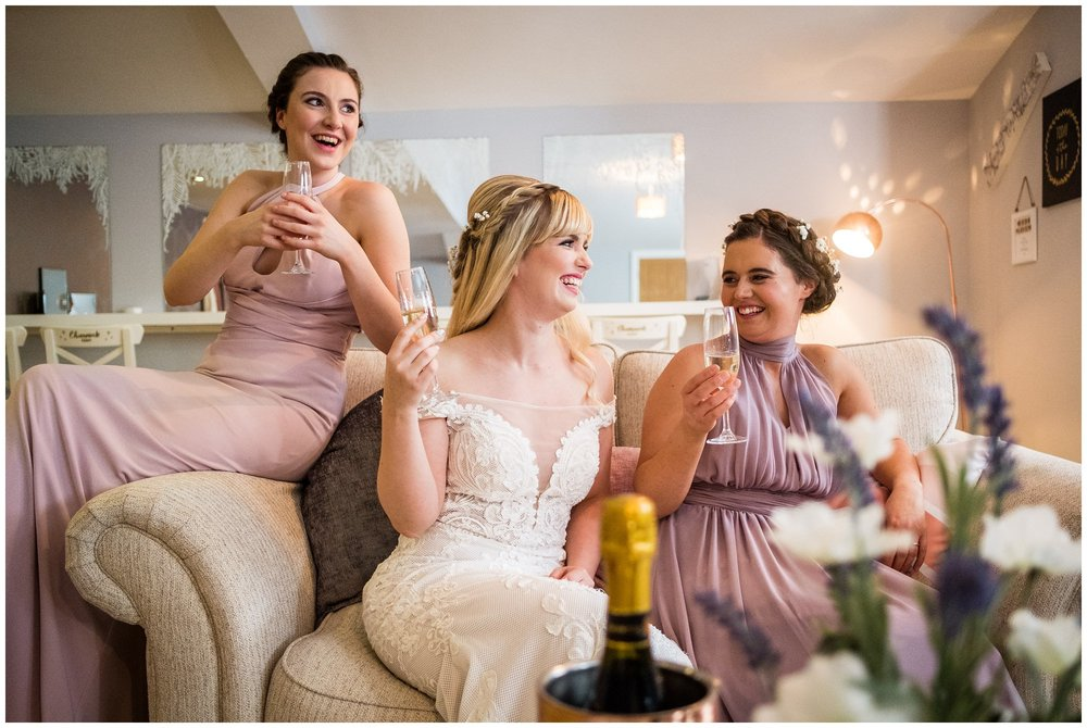 bride and bridesmaids laughing on couch