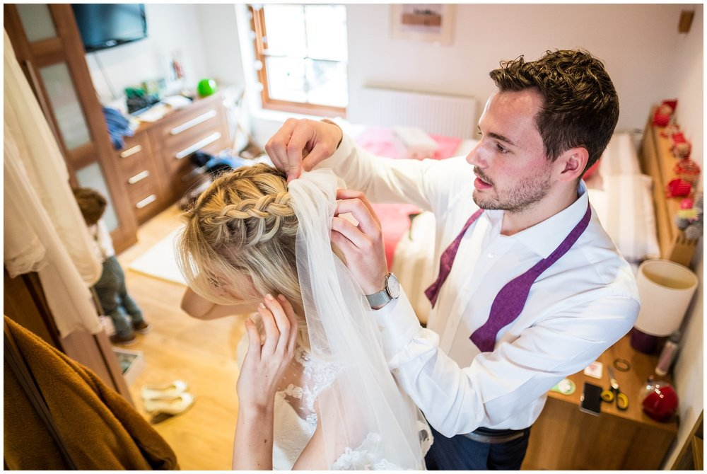 man of honour puts brides veil in