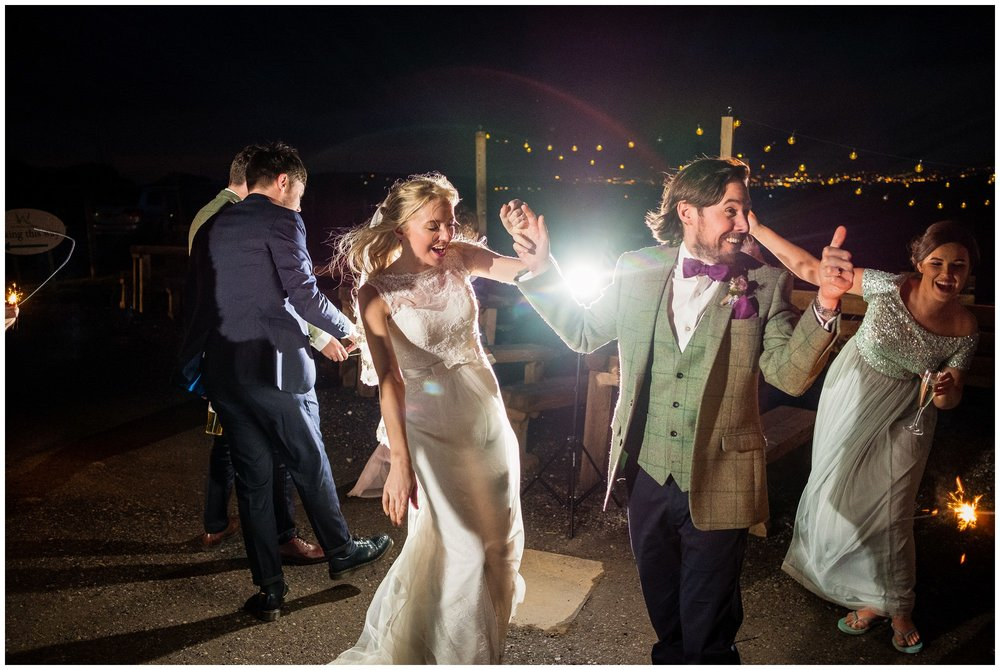 bride and groom dancing outside while setting off sparklers