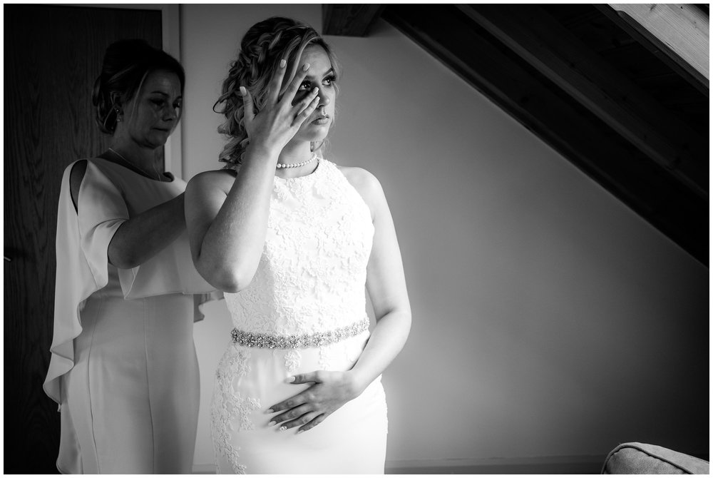 bride crying while mum fastens wedding dress