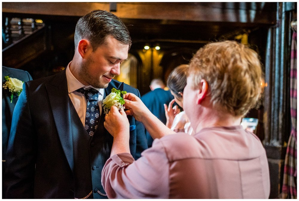 button hole being fastened to groomsmen