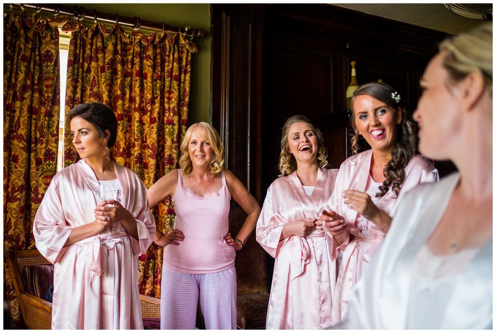 bridesmaids smiling at the bride
