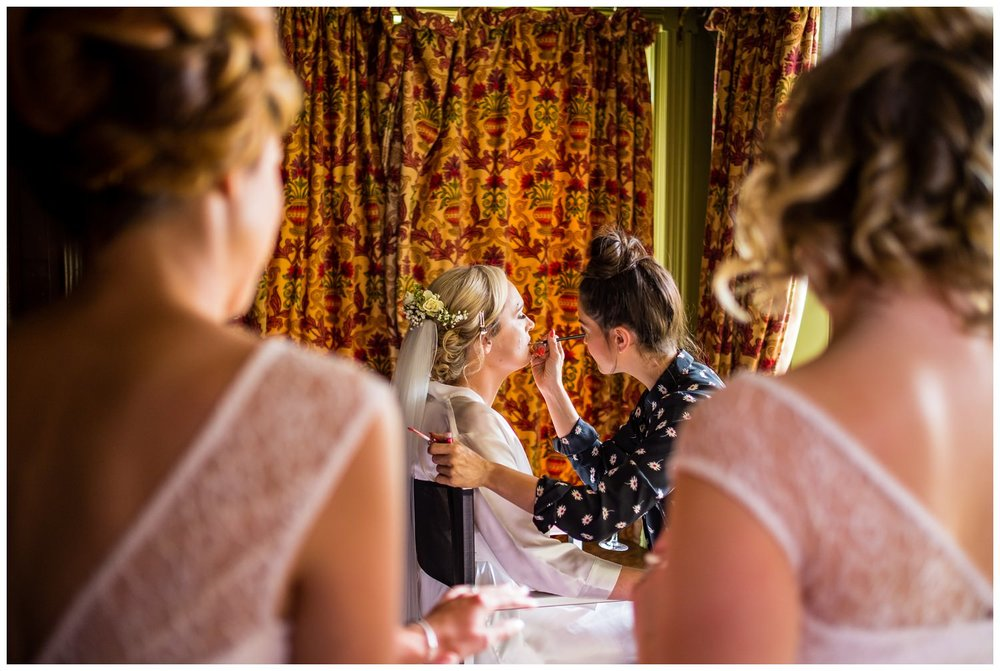 bridesmaids watching bride having her makeup done