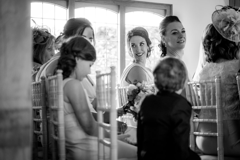 bridesmaid smiling during wedding ceremony