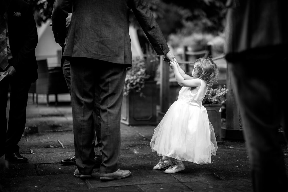 flower girl pulling her dads arm
