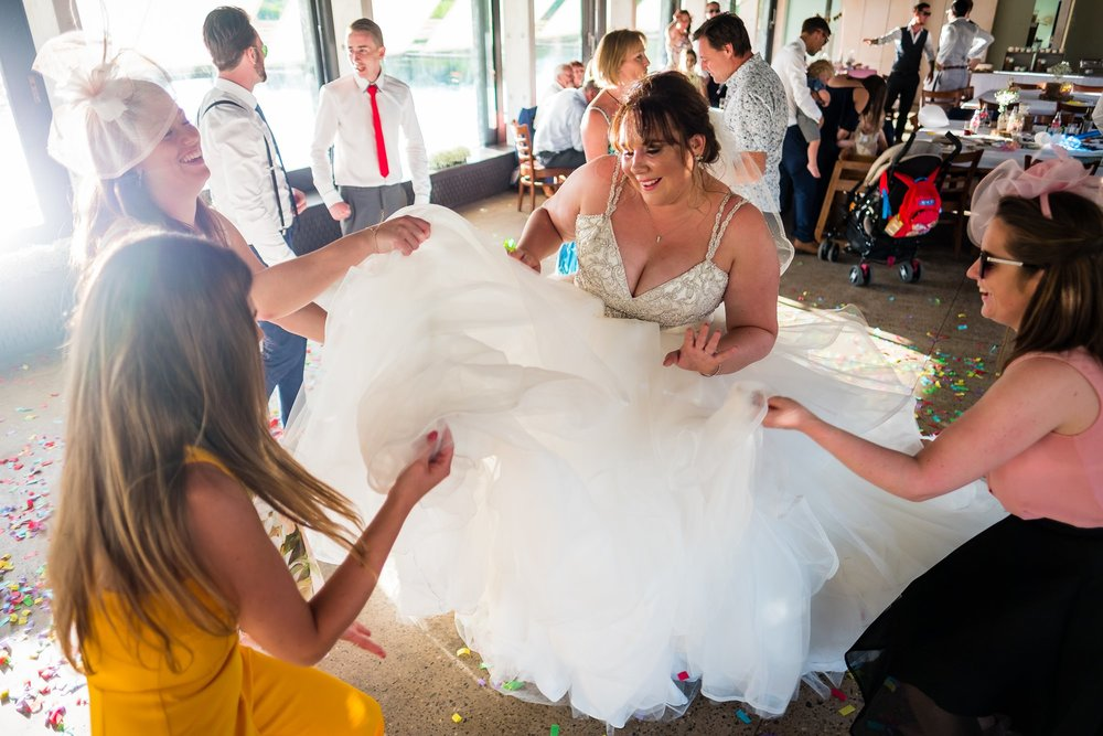girls playing with brides dress