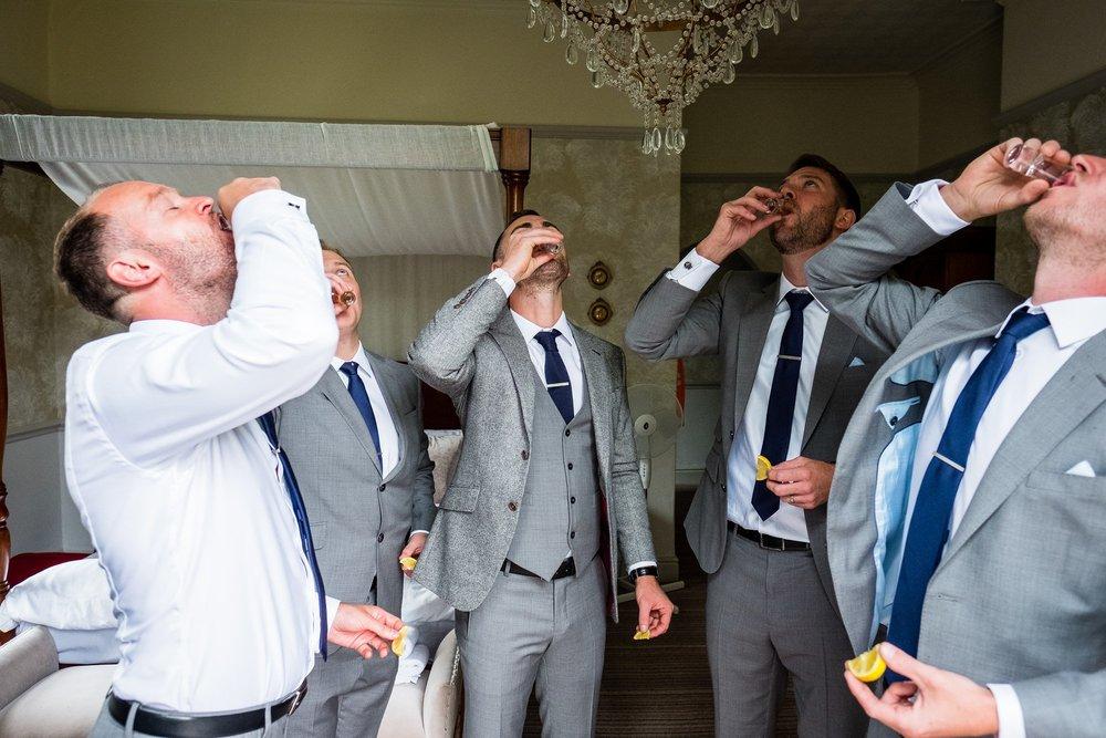 groom and groomsmen doing shots