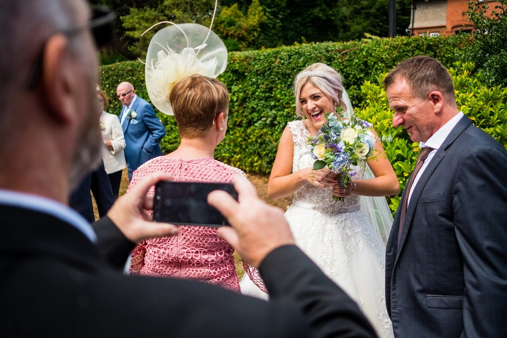 guest taking a photo of bride
