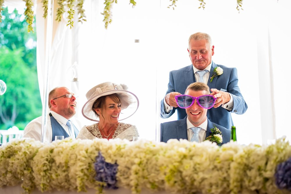 guest putting sun glasses on groom