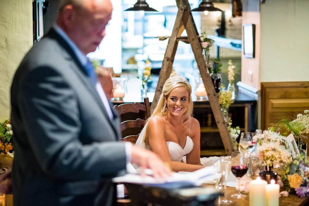bride smiling at dad during speeches