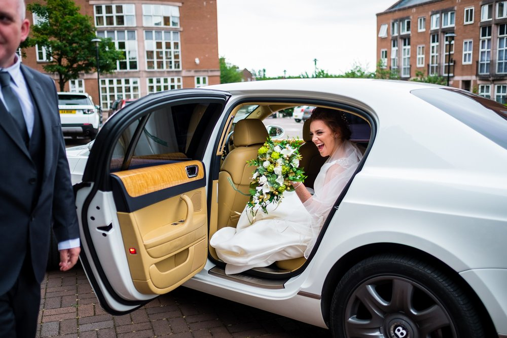 bride getting out of wedding car