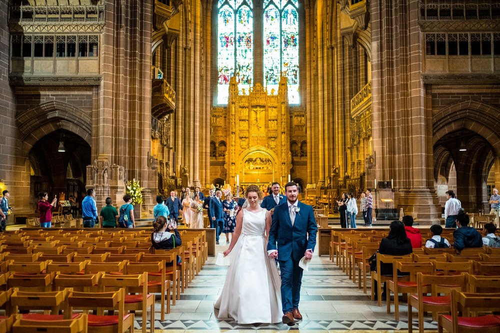 bride and groom walking through Liverpool Cathedral