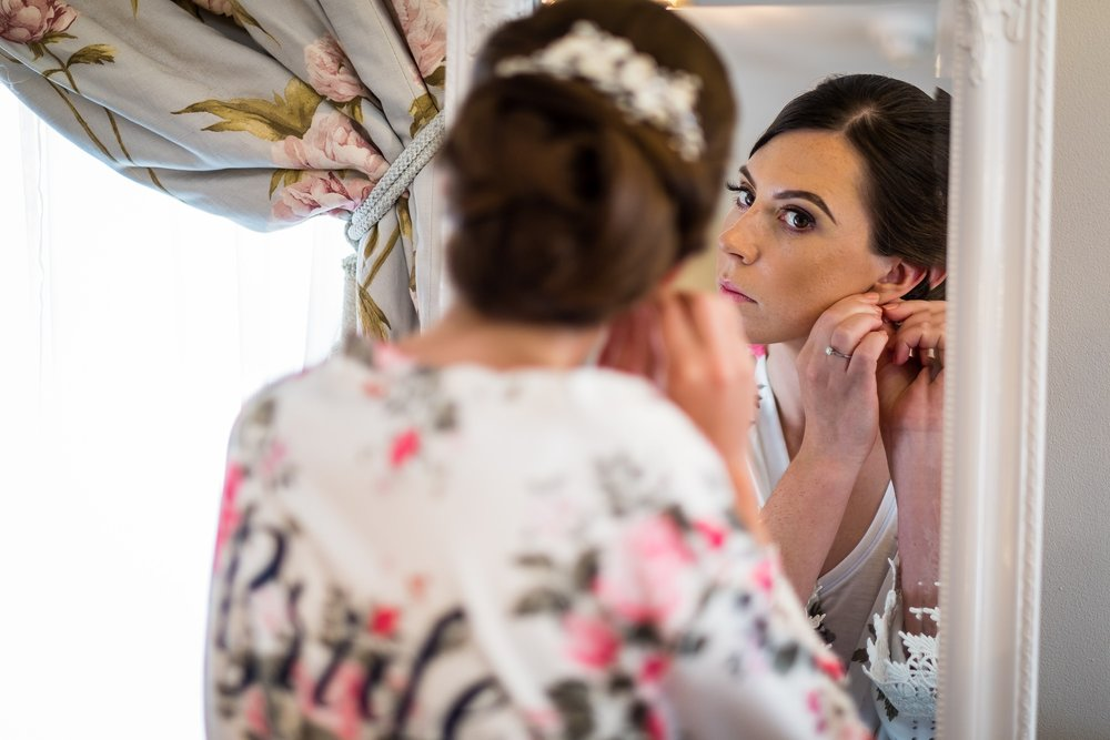bride putting in wedding earrings