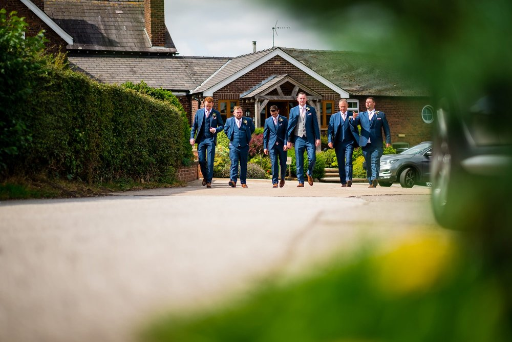 groomsmen walking to the pub