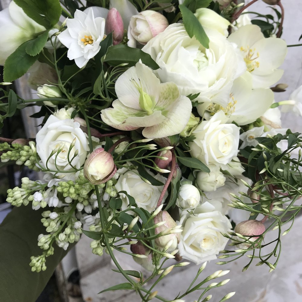 Bridal bouquet of hellebores, white lilac, jasmine and floribundas roses