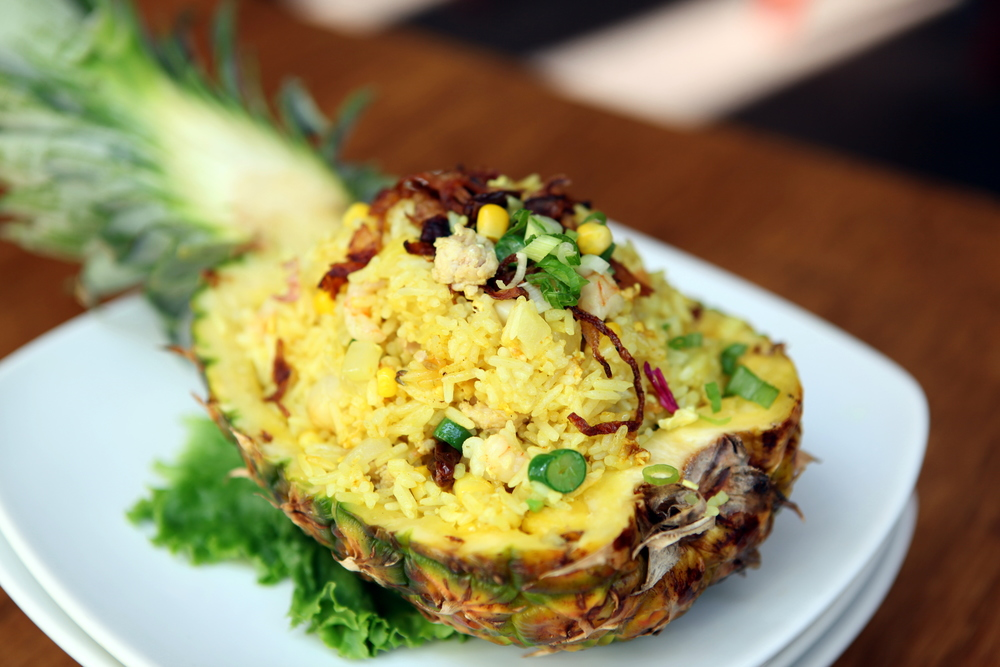 Pineapple Seafood Fried Rice - mixed with seafood, chicken, egg, onion, bean, tomato, raisin, corn, and pumpkin seed.