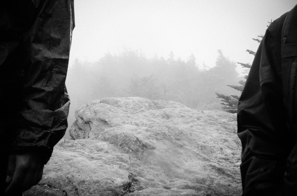 Two students peer out into the fog atop Calloway Peak.