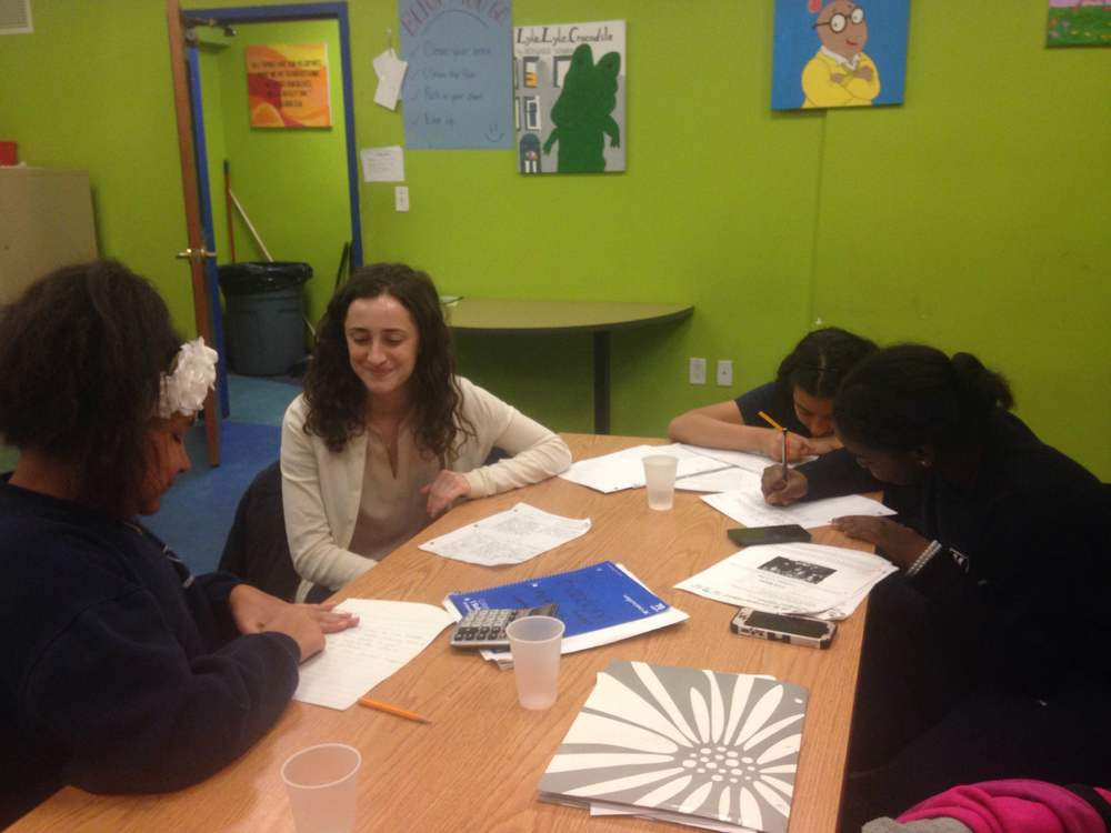 Volunteers from JCRC's ReachOut! program do homework with middle school students