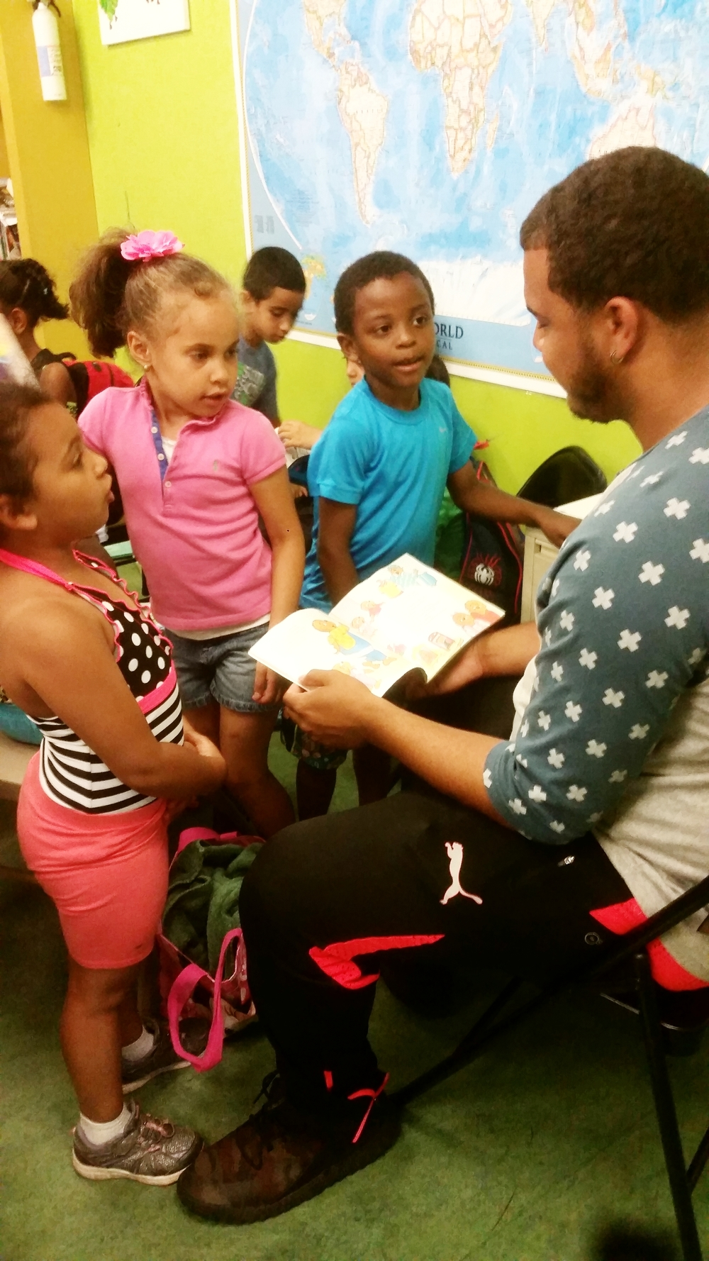 Didier stops by to say hi and volunteers to read with youngest group during DEAR time.