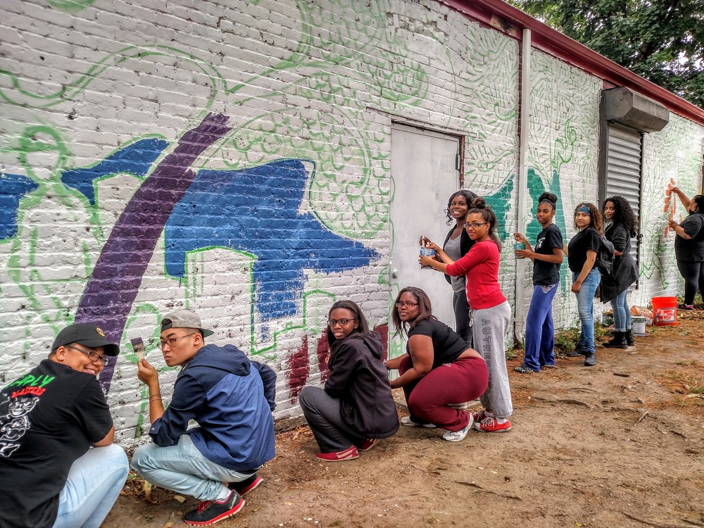Teen organizers work on a mural in Ramsay Park.
