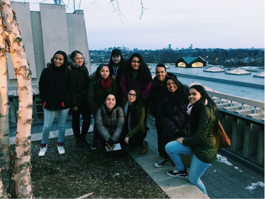 JCITs pose for a picture on the roof of Tisch Library where the city skyline is visible. (Left to right: Rachel, Destiny, Kathleen, Kiara, Taysha, Alejandra, Mara, Alex, Bella, Alicia).