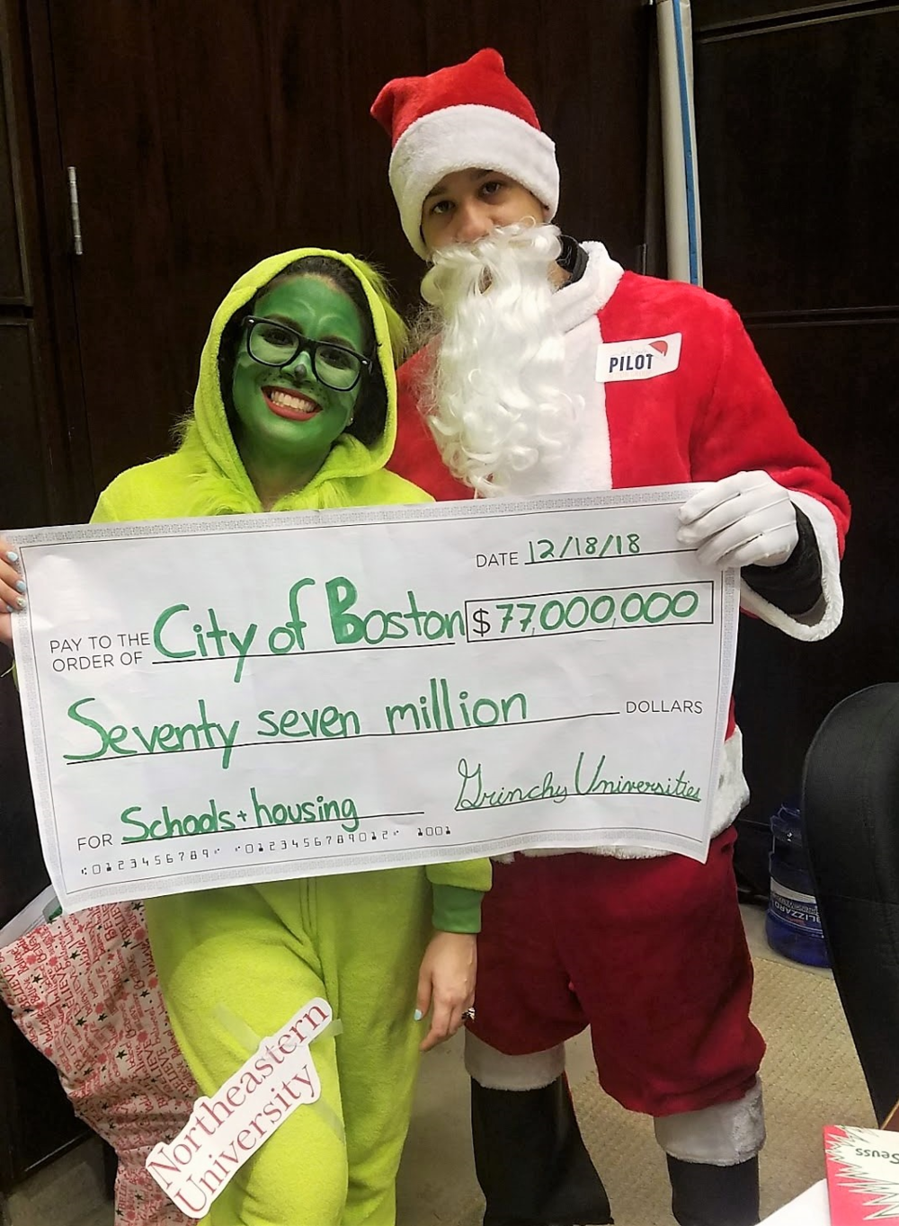 "Delivering a check for the $77 million in unpaid PILOTs from ""Grinchy Universities"" to the City of Boston."