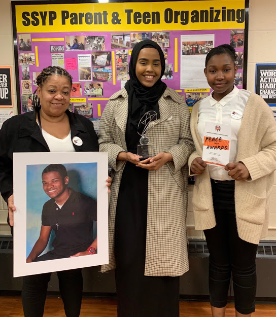 (L to R) Mirna Ramos, holding photo of her son Jorge Fuentes, with B-PEACE leaders Ekran Sharif and Nikkia Jean-Charles