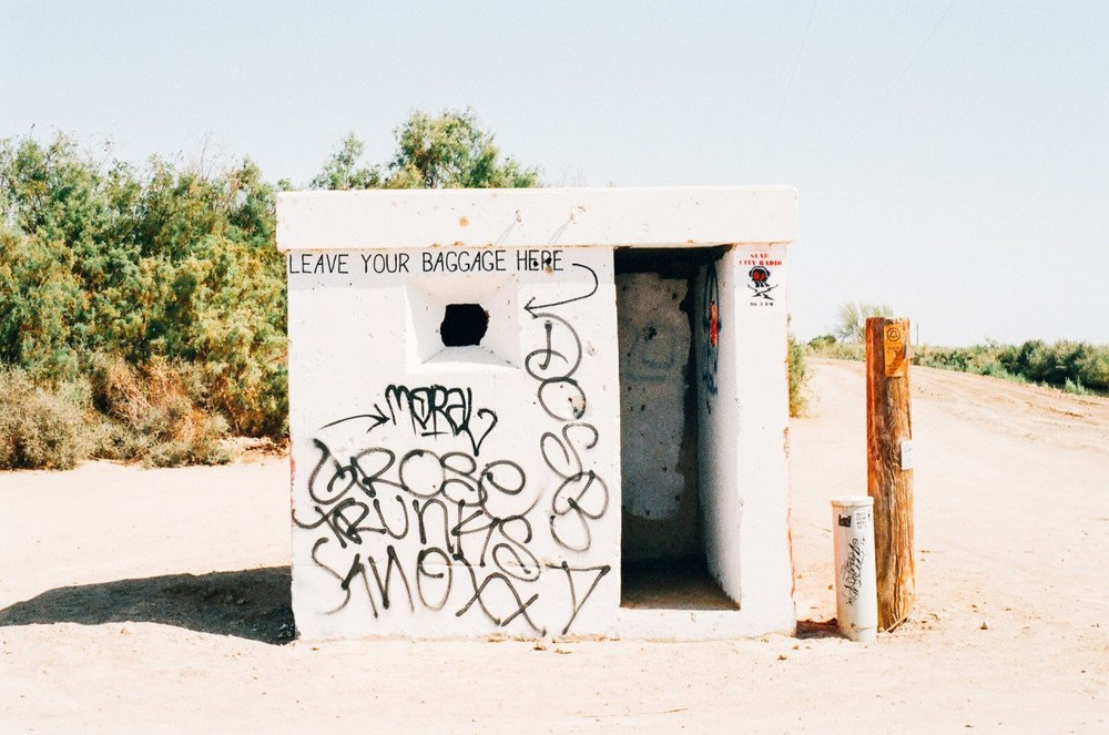 """Hut on beach with graffiti therapy reference """" Leave your baggage here"""" next to a couple poles"""