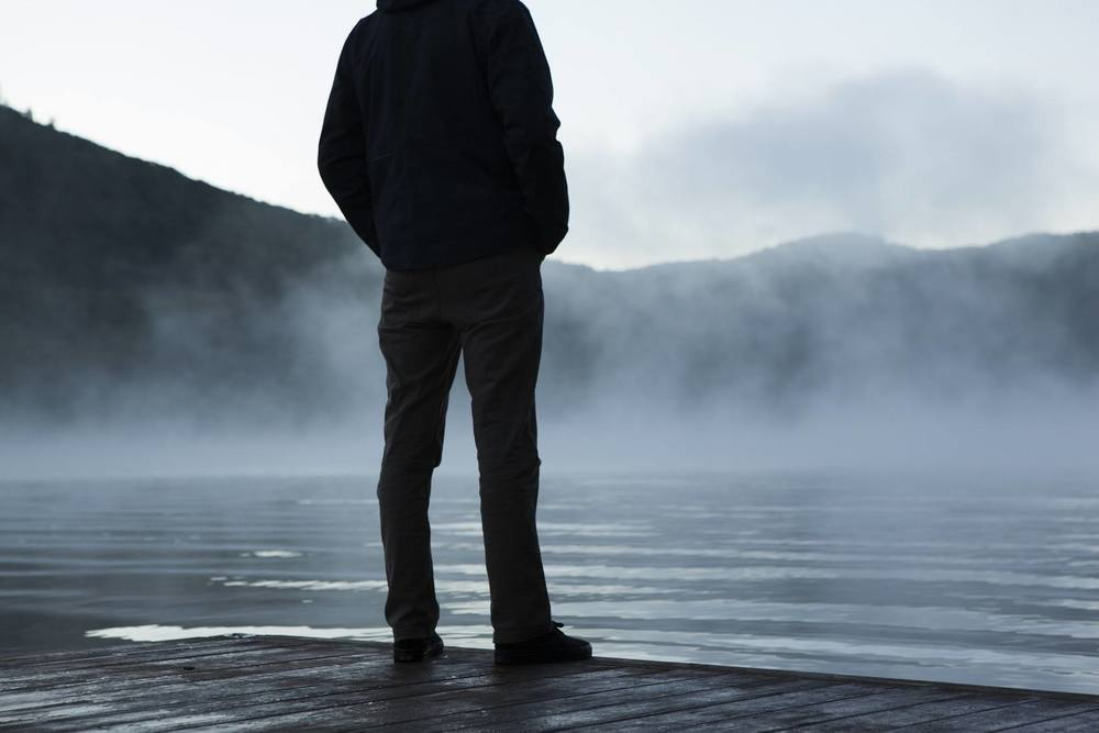 Man standing on dock overlooking a lake and mountains in the mist contemplating life