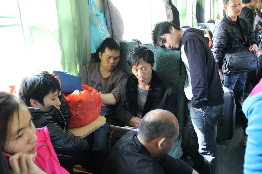 Yuan Zhitong (center) passes the time by watching a movie, aboard the train that will take him and his wife Zhang Junmei home for the first time in one year, to celebrate Chinese New Year. 5 February 2013.