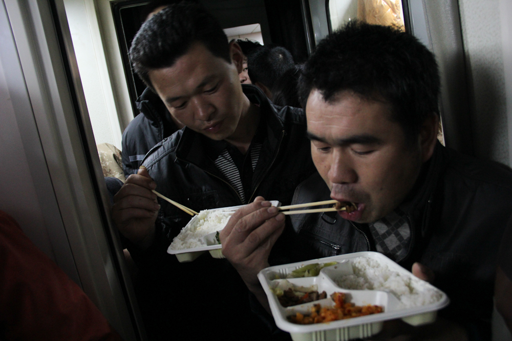 Two men having lunch on the train from Shenzhen to Zhengzhou, February 2013.