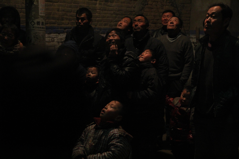 The entire village is gathered outside to watch the traditional fireworks to mark the start of the lunar new year, February 2013.