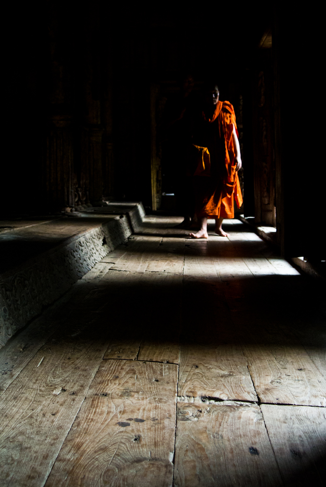 Burmese monk walking inside Shwenandaw monastery in Mandalay, November 2012.