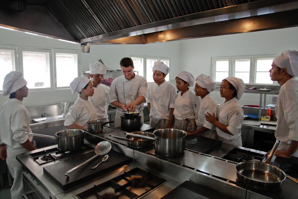 Showing how to use a potato-masher to new cooking students at Shwe Sa Bwe restaurant and cooking school in Yangon, March 2013.