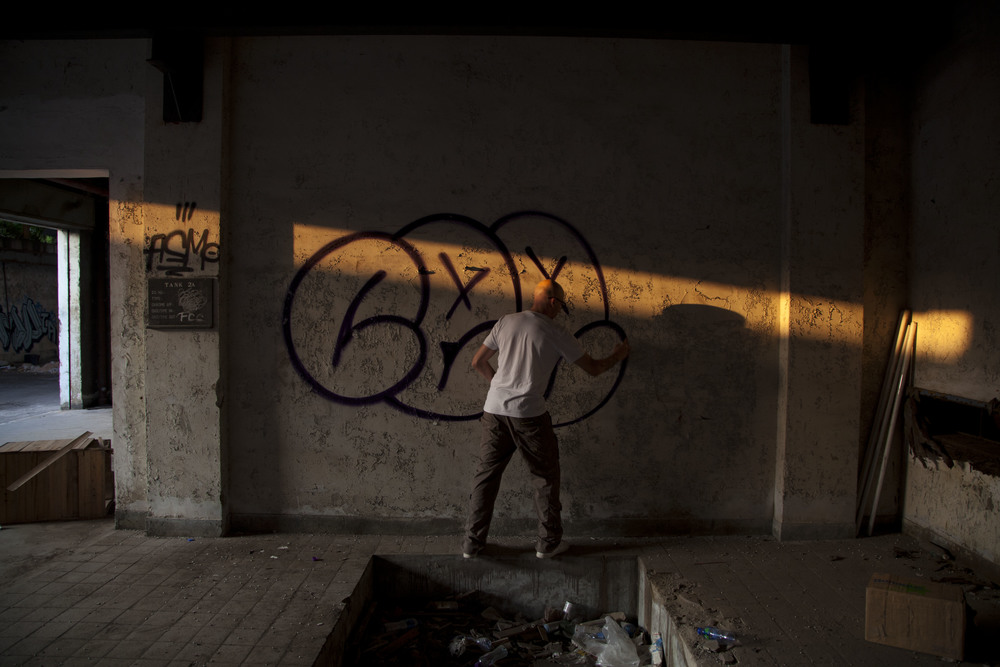 French graffiti artist Ceet paiting in an abandoned factory building near Kwun Tong, December 2011.