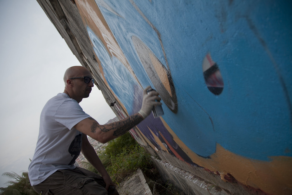 Ceet, a French graffiti artist, painting on a wall outside an abandoned factory building near Kwun Tong, December 2011.