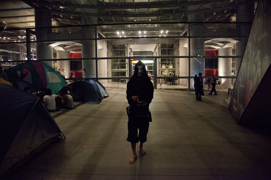 "A protester wearing a Guy Fawkes mask is walking near the ""Occupy Central"" camp under the HSBC building in Central, October 2011."