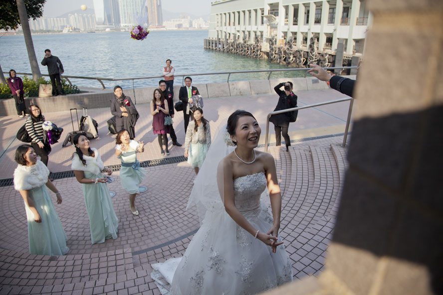 A bride throws the bouquet to her bridesmaids on her wedding day, Central Ferry pier, on December 25, 2011.