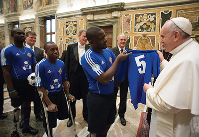 Wilfrid presenting the Pope with a Haitian Soccer Jersey on the 5th anniversary of the Haiti earthquake, in Rome.