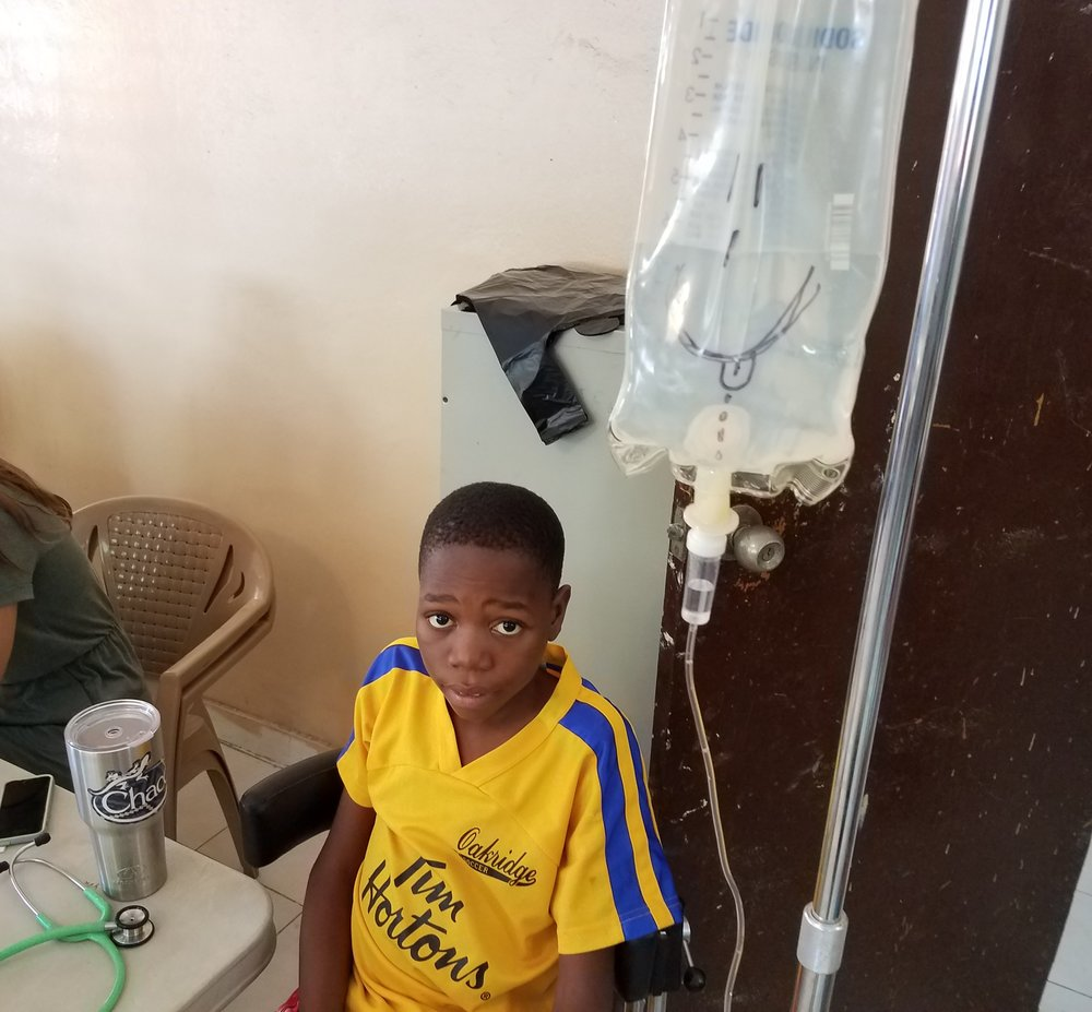 "Jackenson getting a ""Piki"" during a Sickle Cell crisis but still wanting to be in the clinic.  He didn't see the humor in my artwork on his IV bag."