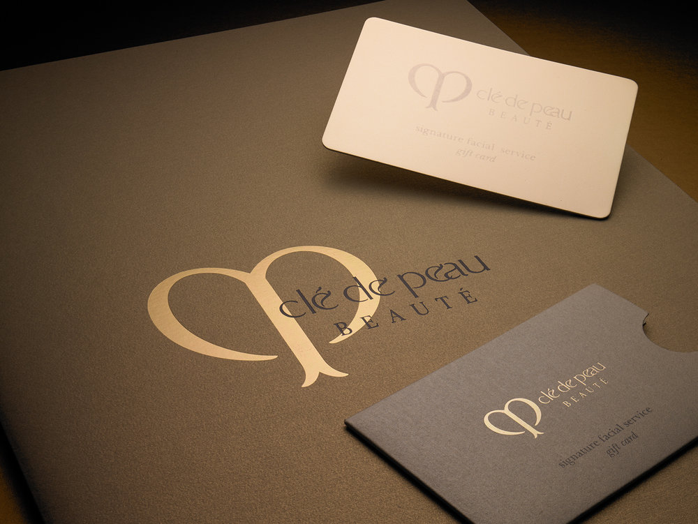 Clé de Peau Beauté Gift Card & Sleeve   Clé de Peau is Shiseido's high-end cosmetic brand. We made them a double-thick, foil-stamped gift card on gold foil cover stock to add a more substantial feeling to their promotion. The four corners were diecut round and the sleeve was printed on a pearlized cover sheet. Printing included a PMS gray and gold foil-stamped logo. It was diecut with a crescent thumb cut.