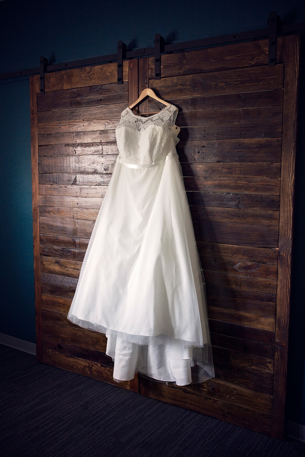 Bride's dress hangs on old barn door inside the Northside Church of Christ, Harrison Arkansas Wedding Photography