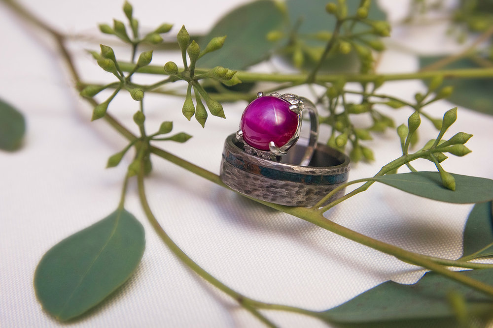 wedding ring with purple stone and grooms wedding band on reception table greenery