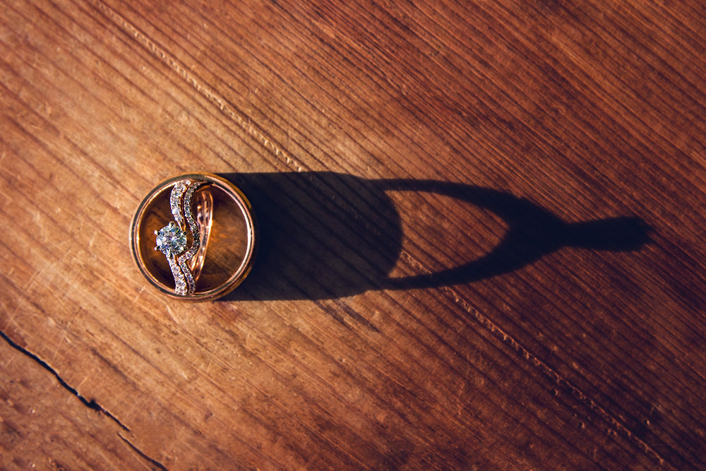 Gold wedding rings casting shadow on wood, lit by setting sun.