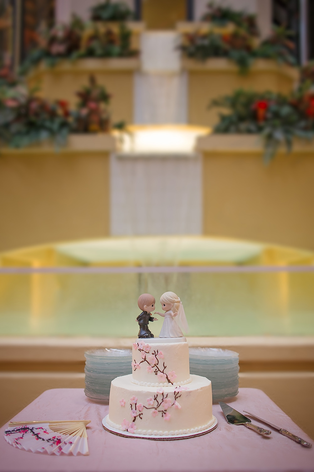 Pink cherry blossoms adorn this wedding cake with a Precious Moments cake topper - Holiday Inn Hotel & Suites Wedding Reception