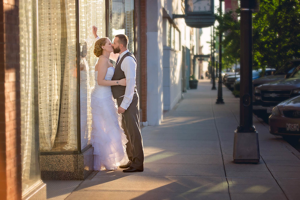 Bride and groom share a kiss in the sunset on historic Commercial Street outside of the Savoy Ballroom