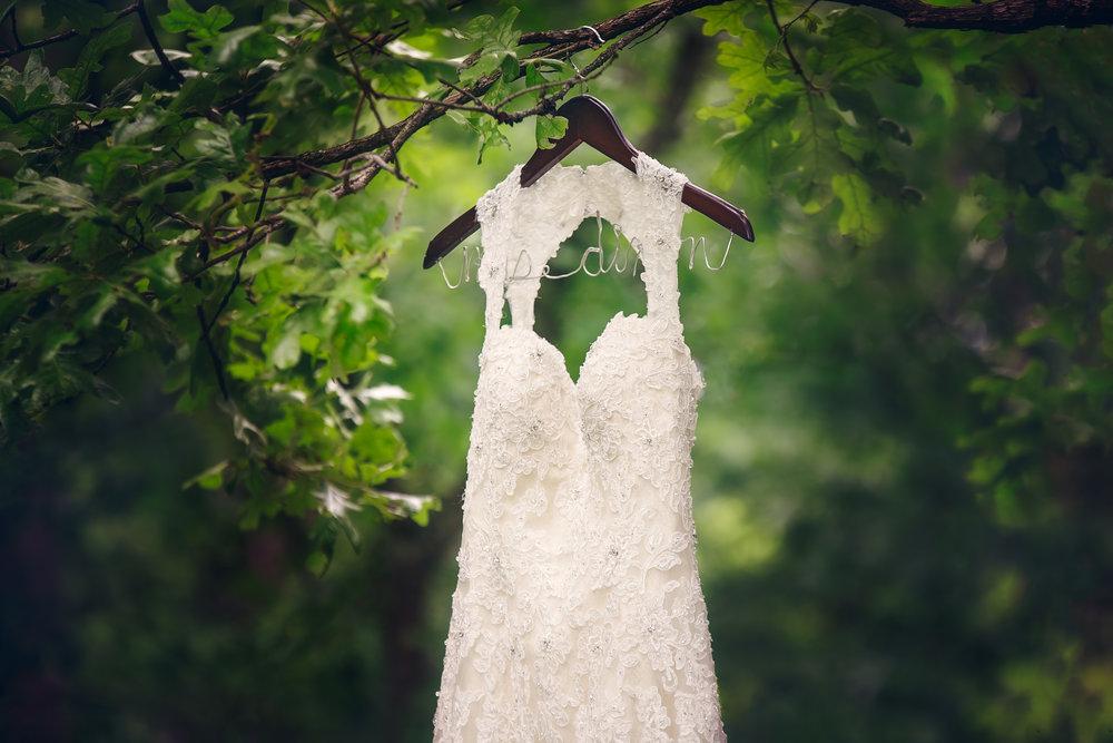Aly's wedding dress hangs near the wedding party cabin at Camp Pin Oak, Kaiser MO