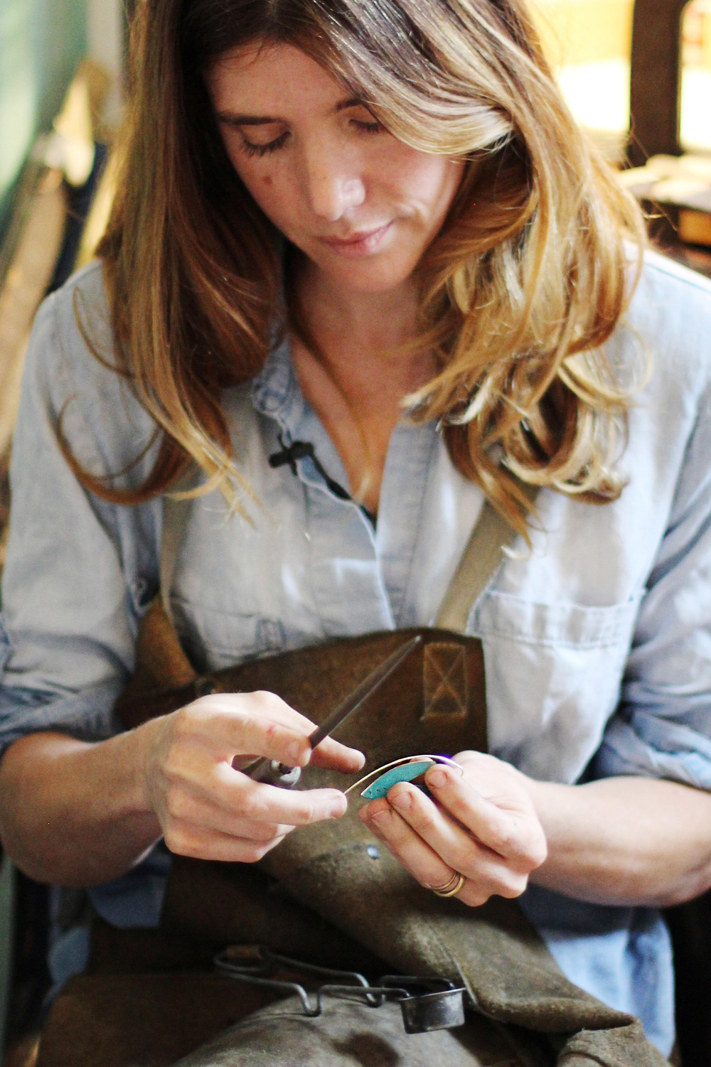 Copper Collection jewelry, an Art of Travel exclusive, is BACK by popular demand.  Shop stunning legacy jewelry pieces and accessories designed for both men and women. Crafted from salvaged pieces of Lambert's historic and iconic original copper roof, the collection features works from local artists Jennifer Walker, Peg Fetter, Roger Rimel and Leia Zumbro. Photo: Jeweler Jennifer Walker working on a 2016 Copper Collection piece.