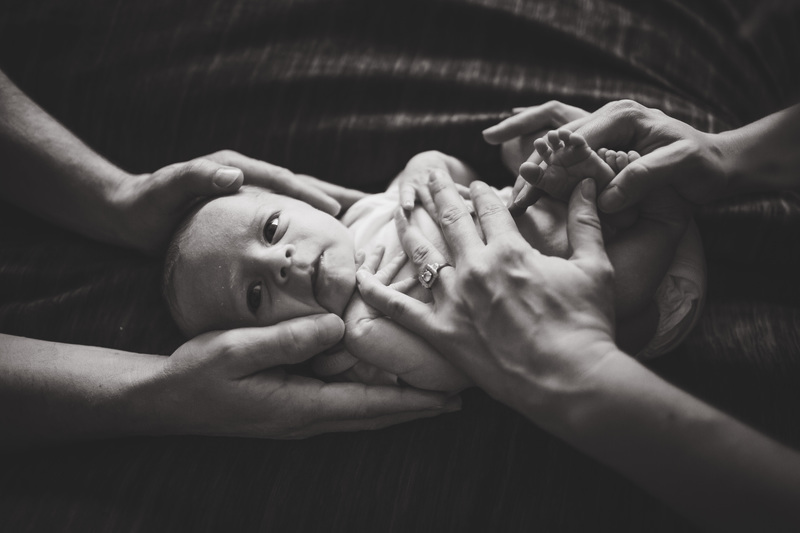 newborn posing with parents hands on baby elena s blair photography