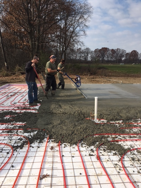 Pouring Concrete for the floor of the house over the tubing for radiant heat.